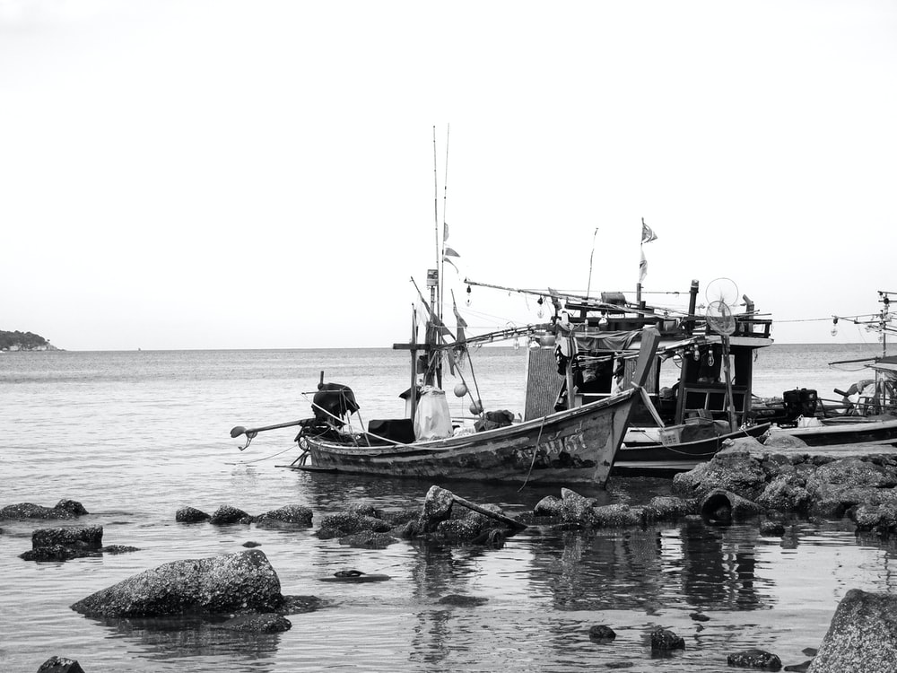 grayscale photo of people riding boat on water