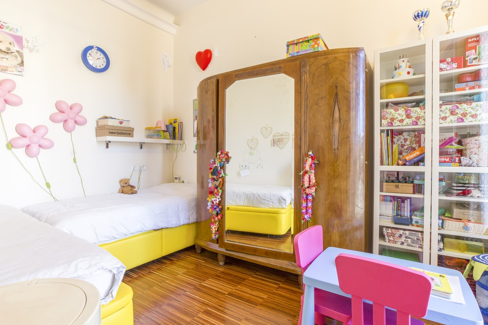 brown wooden cabinet beside white bed