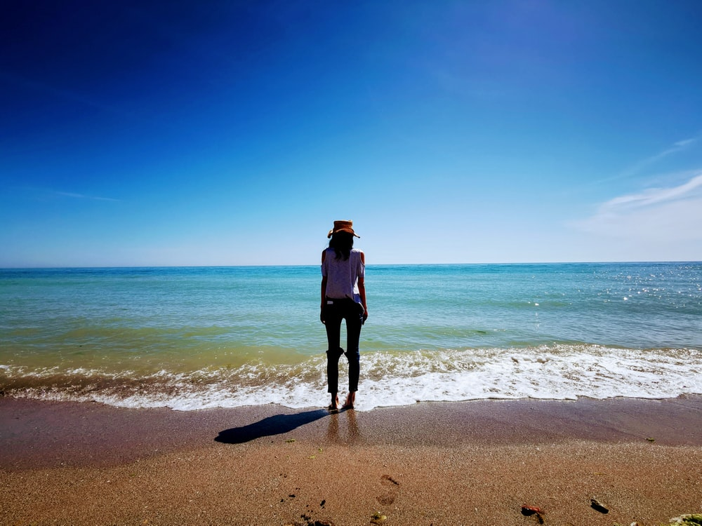 woman in black jacket standing on beach during daytime