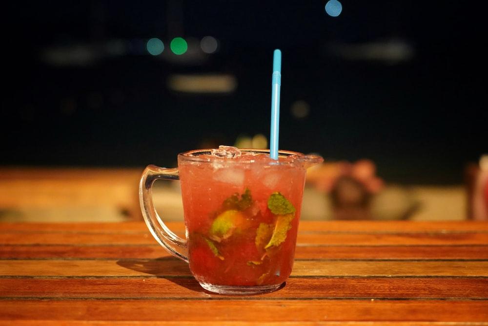 clear glass mug with orange liquid and white straw