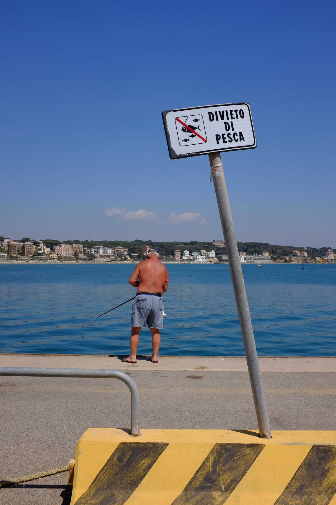 A man is fishing under a sign that prohibits fishing