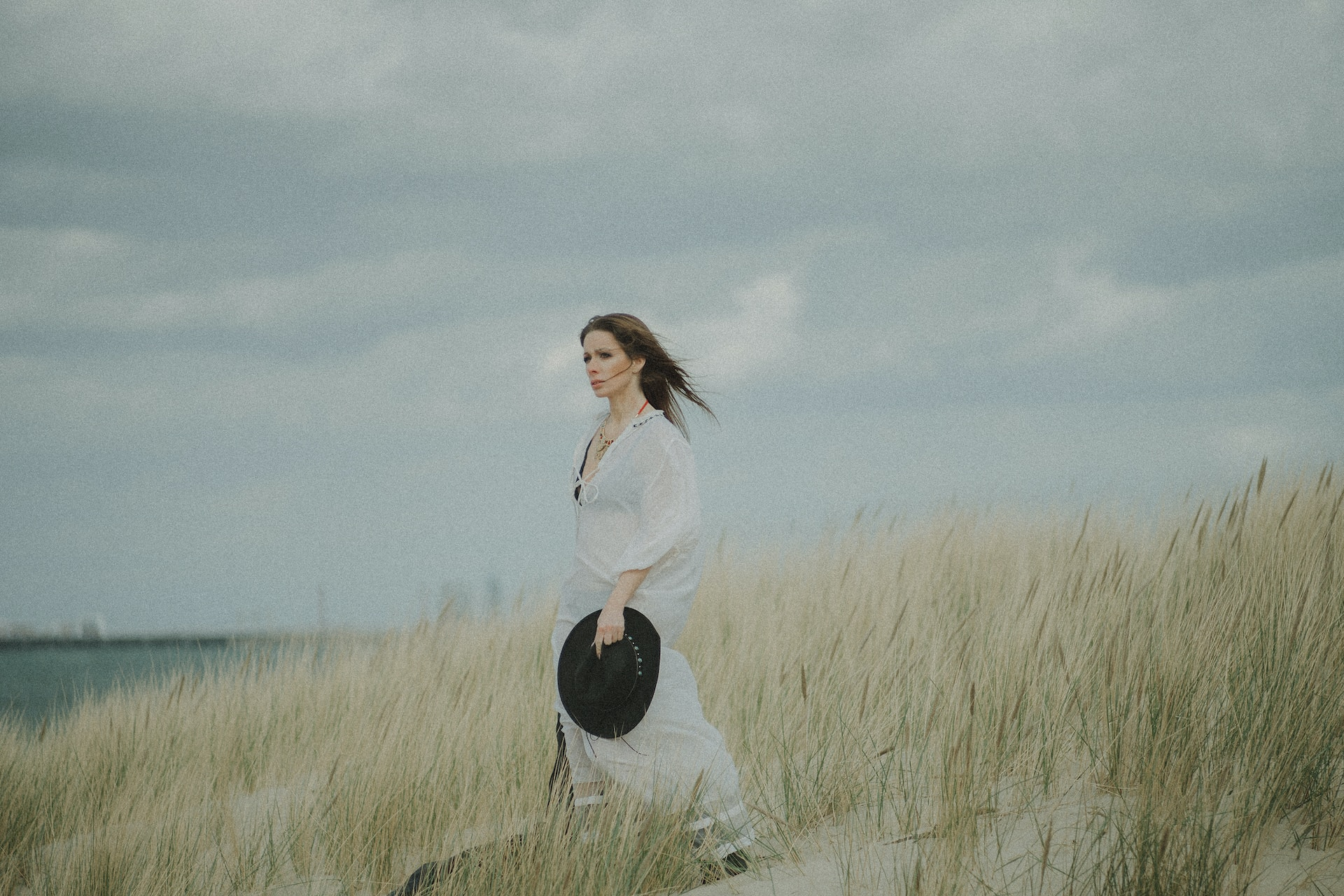 woman in white long sleeve shirt and black pants standing on green grass field under gray