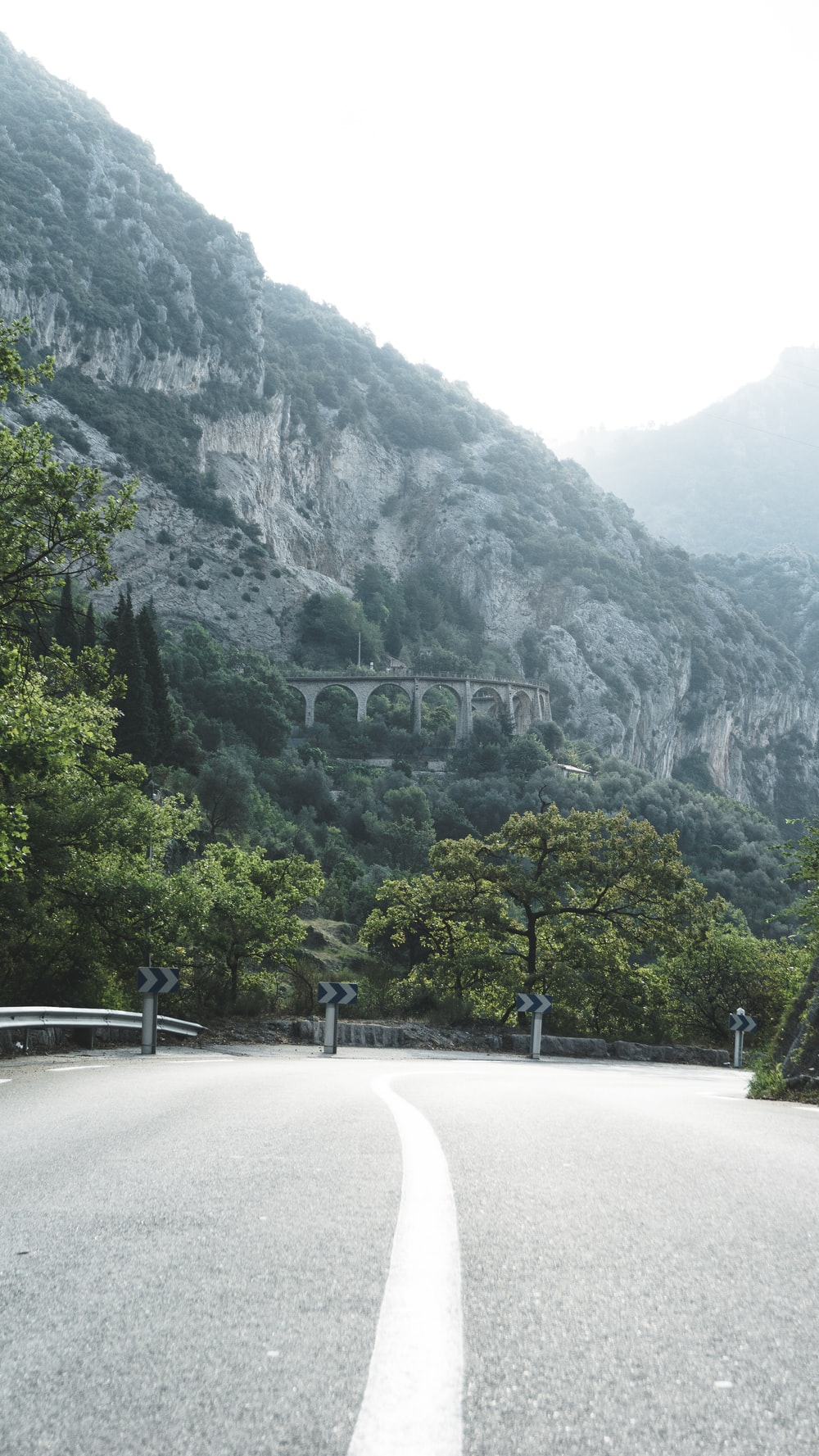 gray concrete road near green trees and mountain during daytime
