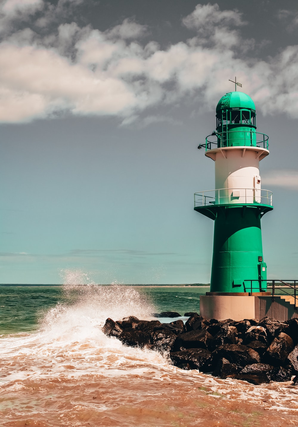 green and white lighthouse on brown rock formation beside sea during daytime