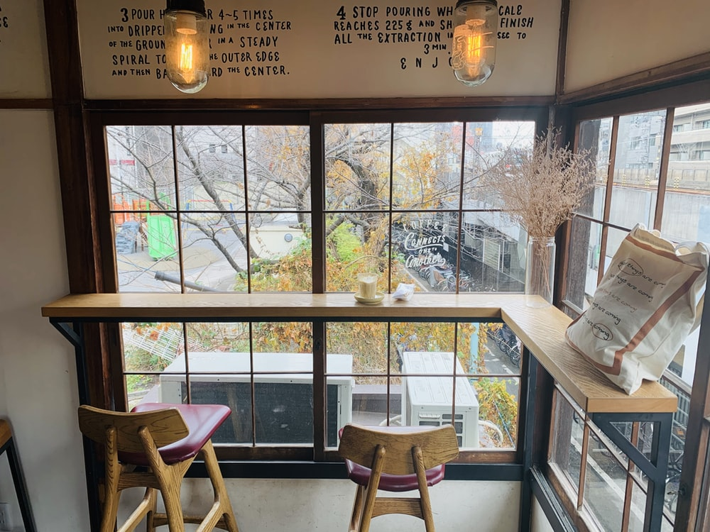 brown wooden table near glass window