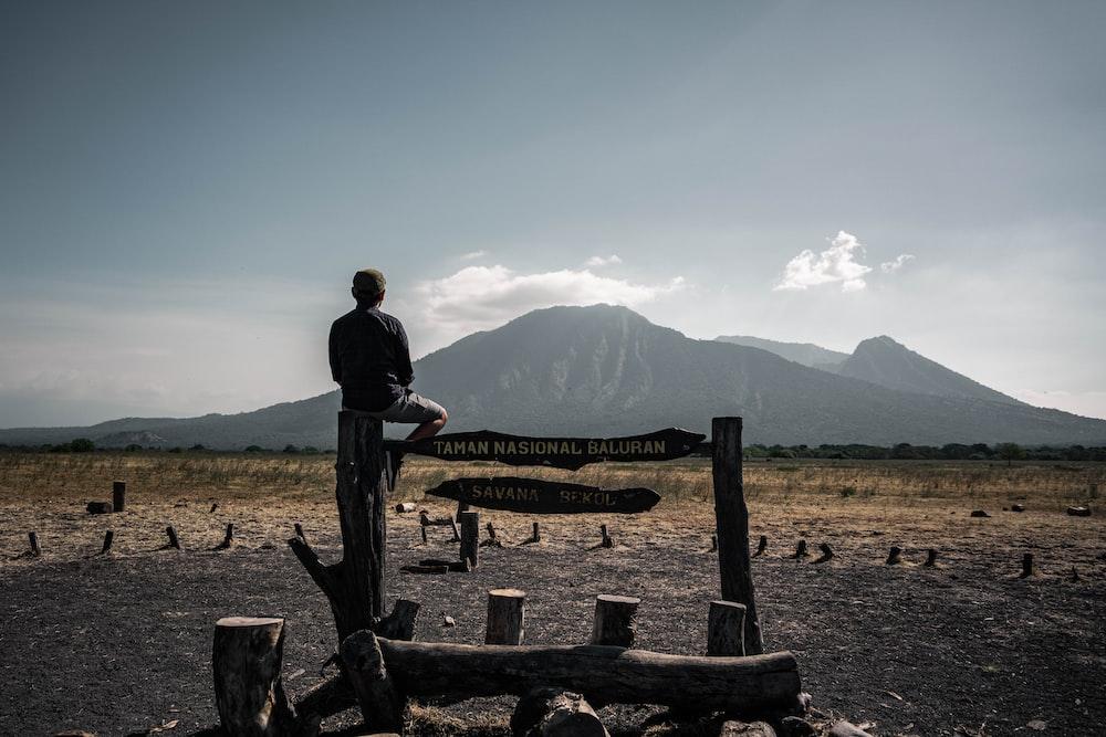 man in black jacket sitting on brown wooden bench during daytime