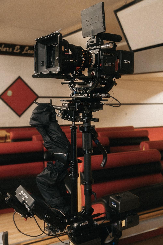 man in black jacket and pants holding black dslr camera