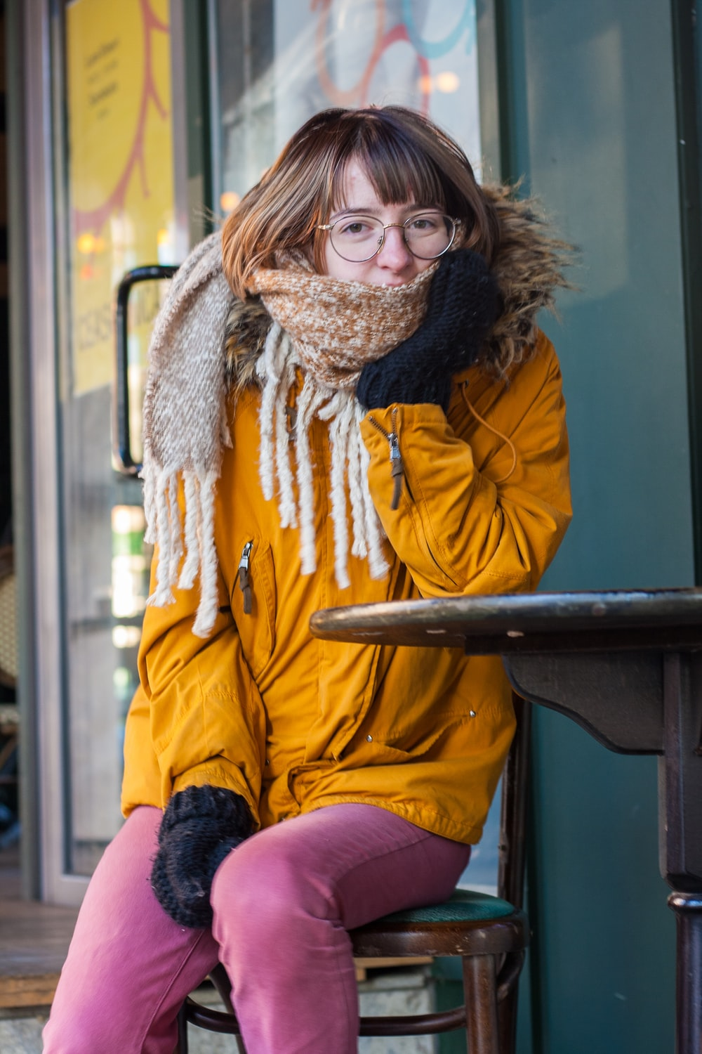 woman in yellow jacket wearing brown scarf and black framed eyeglasses