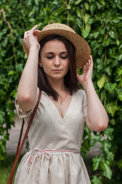 woman in white sleeveless dress wearing brown sun hat