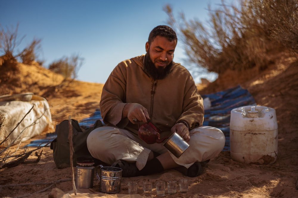 man in brown jacket sitting on sand during daytime