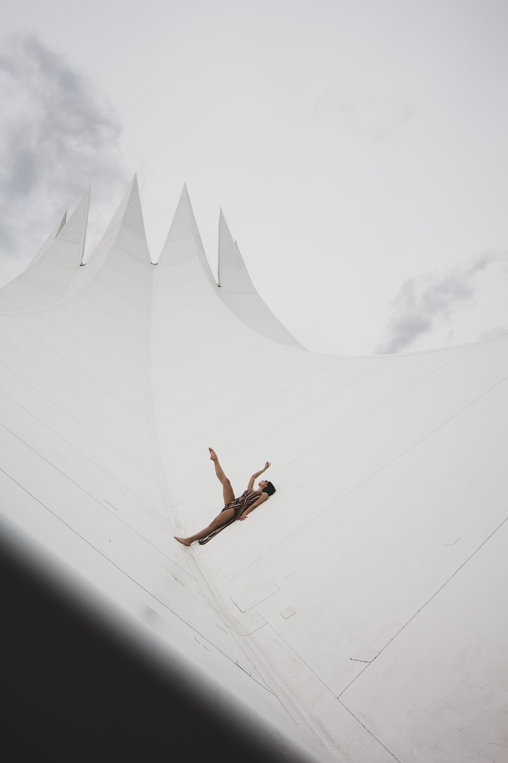 man in black shorts jumping on white concrete wall during daytime