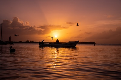 silhouette of 2 people riding on boat during sunset belize teams background