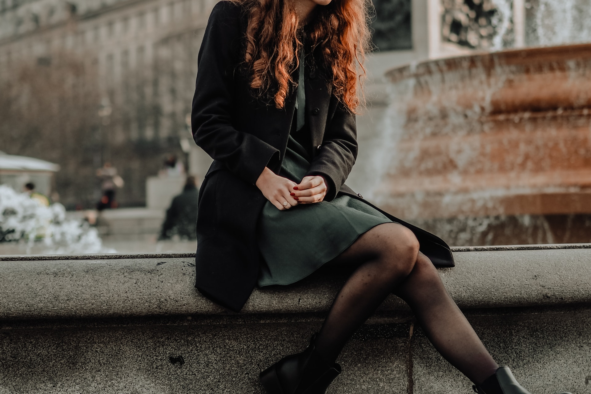 woman in black coat sitting on concrete bench during daytime
