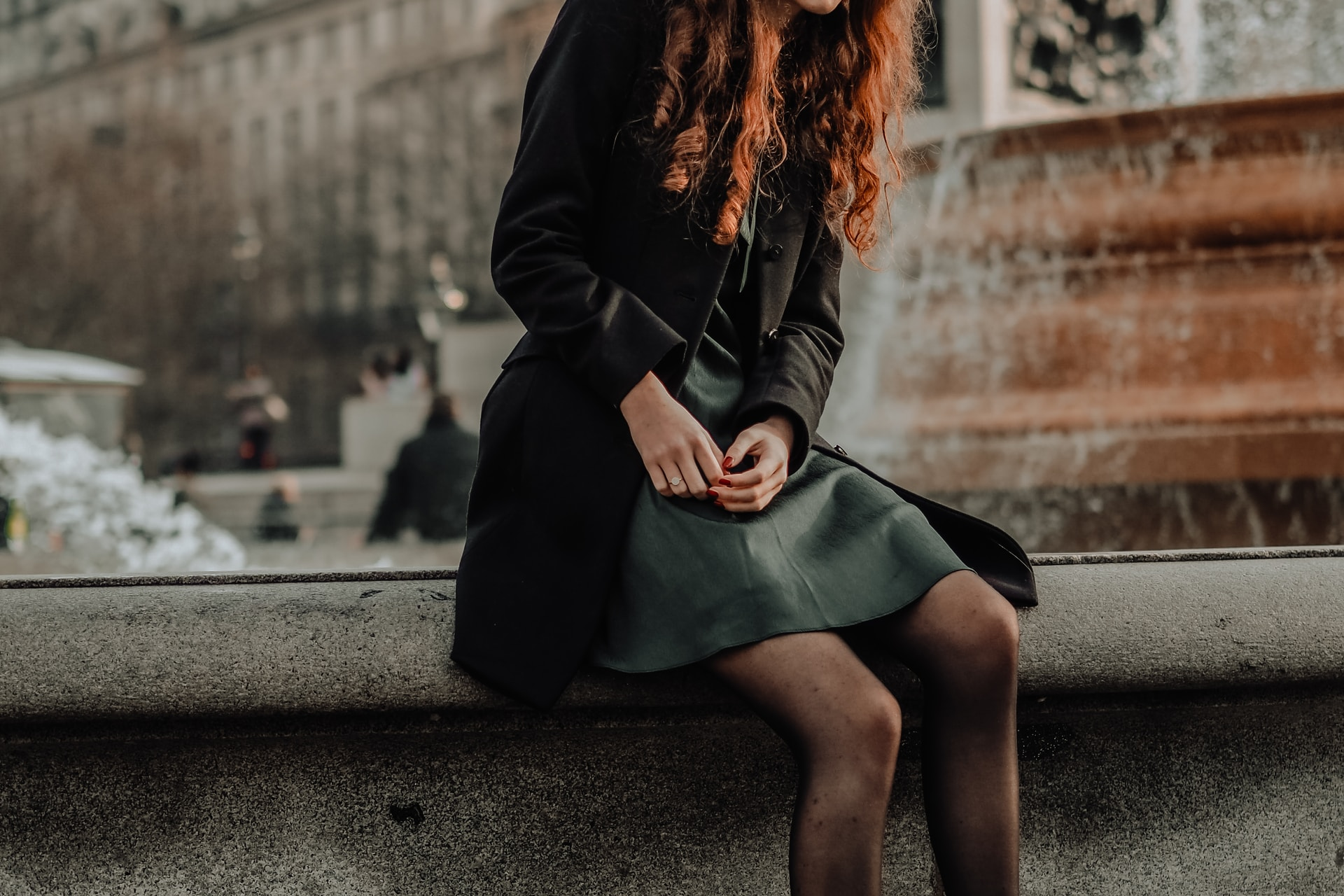 woman in black long sleeve dress sitting on gray concrete bench during daytime