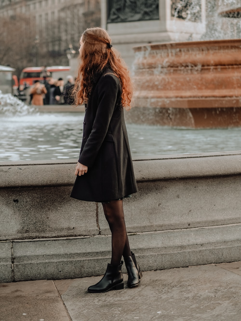 woman in black coat standing on concrete pavement during daytime
