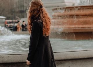 woman in black coat standing on concrete bridge during daytime