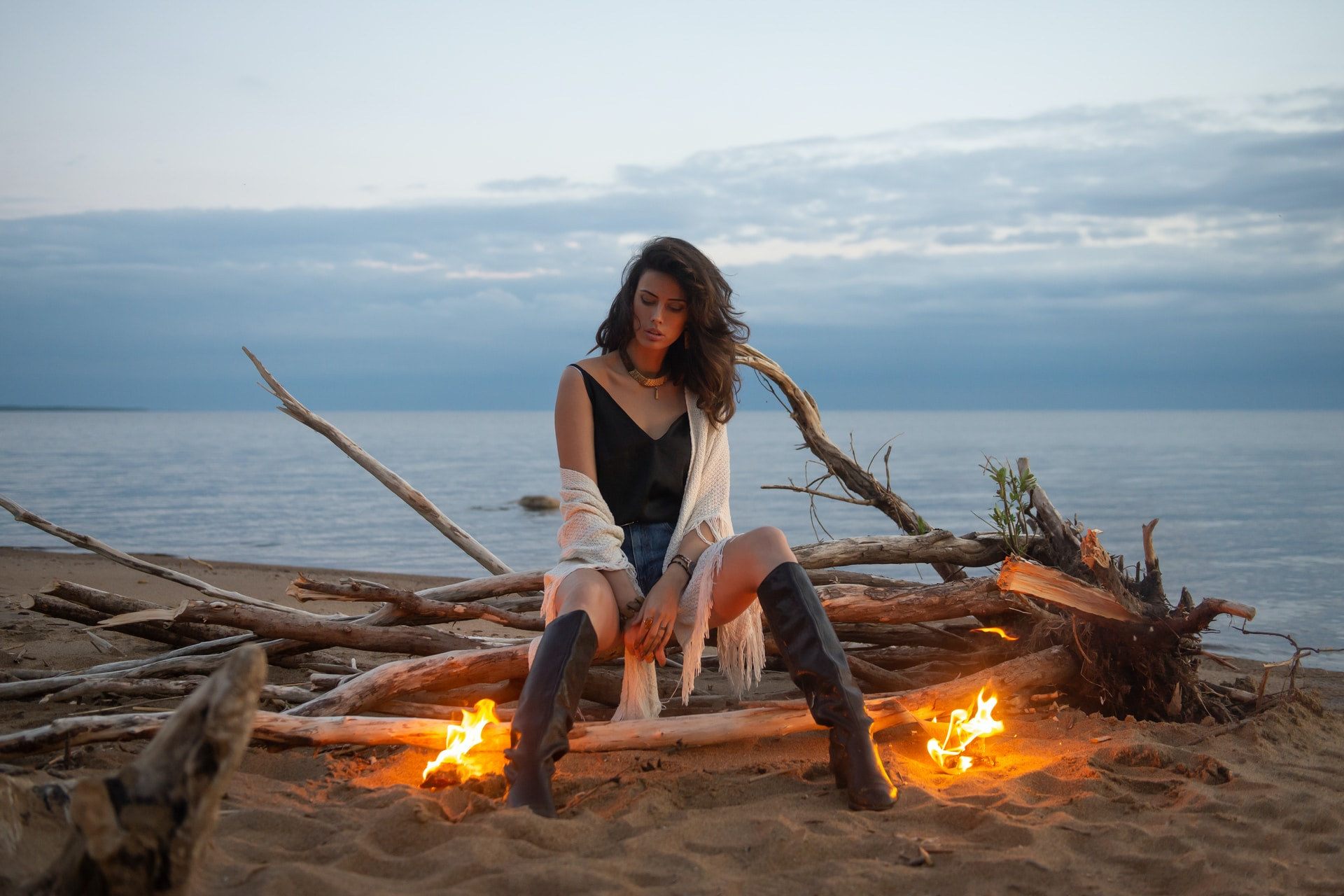 woman in white tank top sitting on brown log near bonfire during daytime