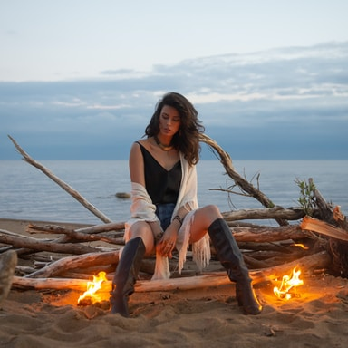 woman in white tank top sitting on brown log near bonfire during daytime