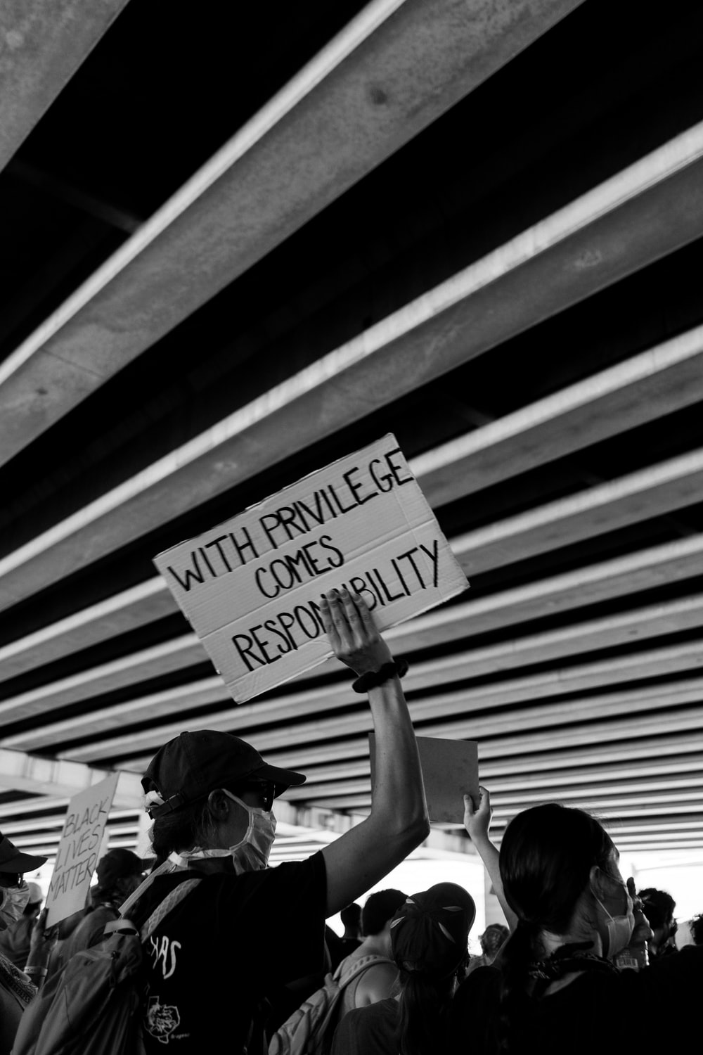 grayscale photo of woman holding sign