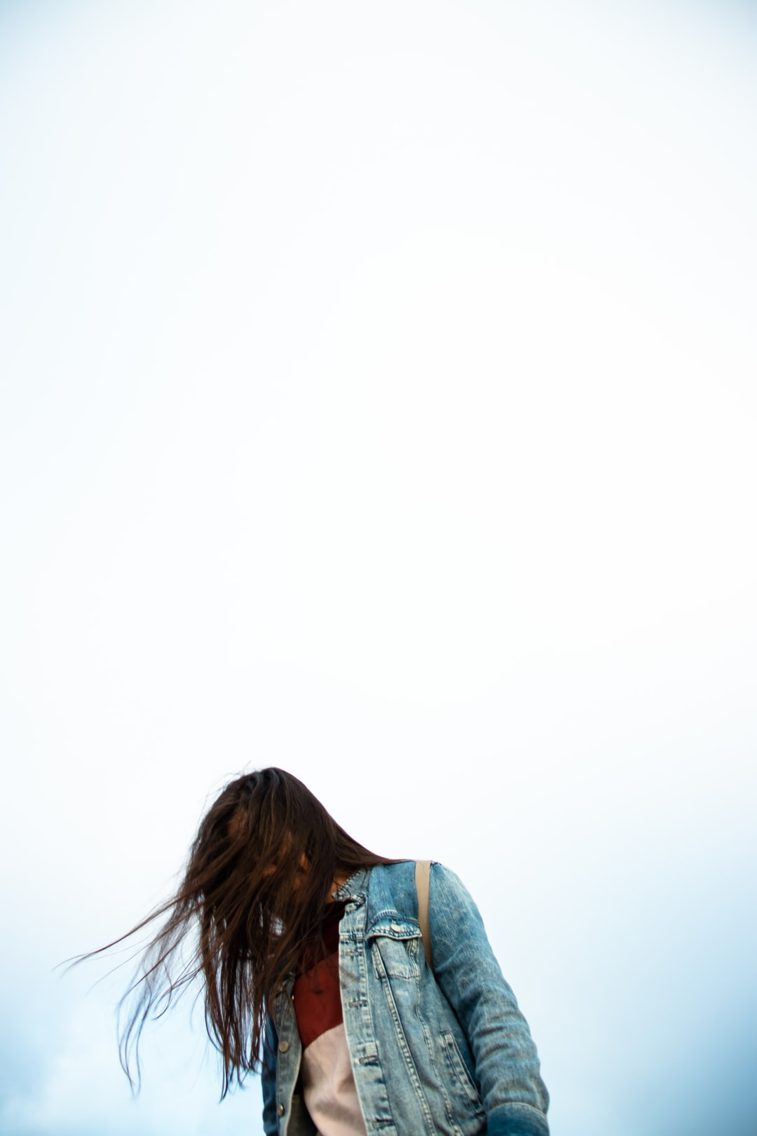 Instagram| @jordanniranjan  Girl with brown hair looking down with the wind blowing through her hair. The background is foggy with hints of blue from clouds clearing up on top the mountain.