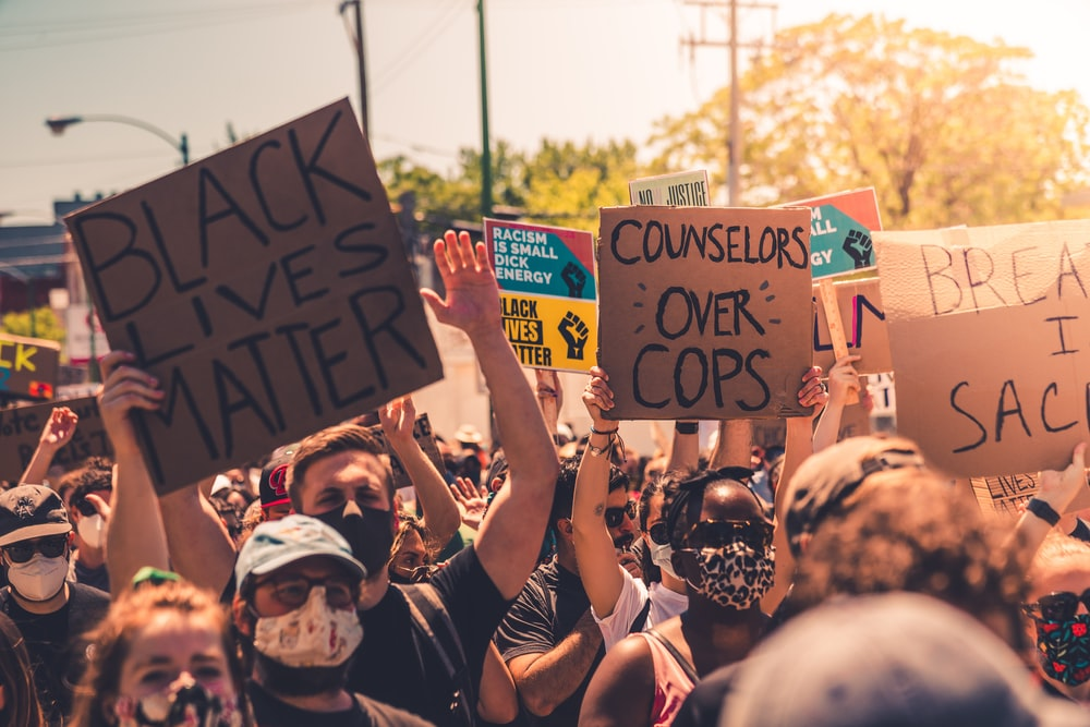 people holding black and blue banner during daytime