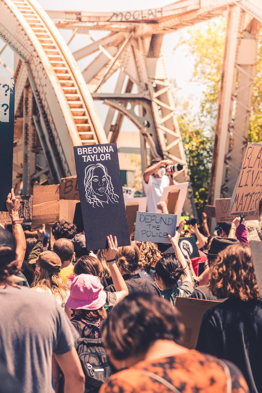 people holding signage during daytime