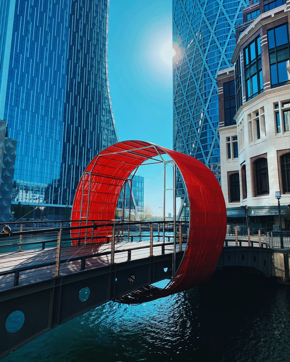 red arch near high rise building during daytime