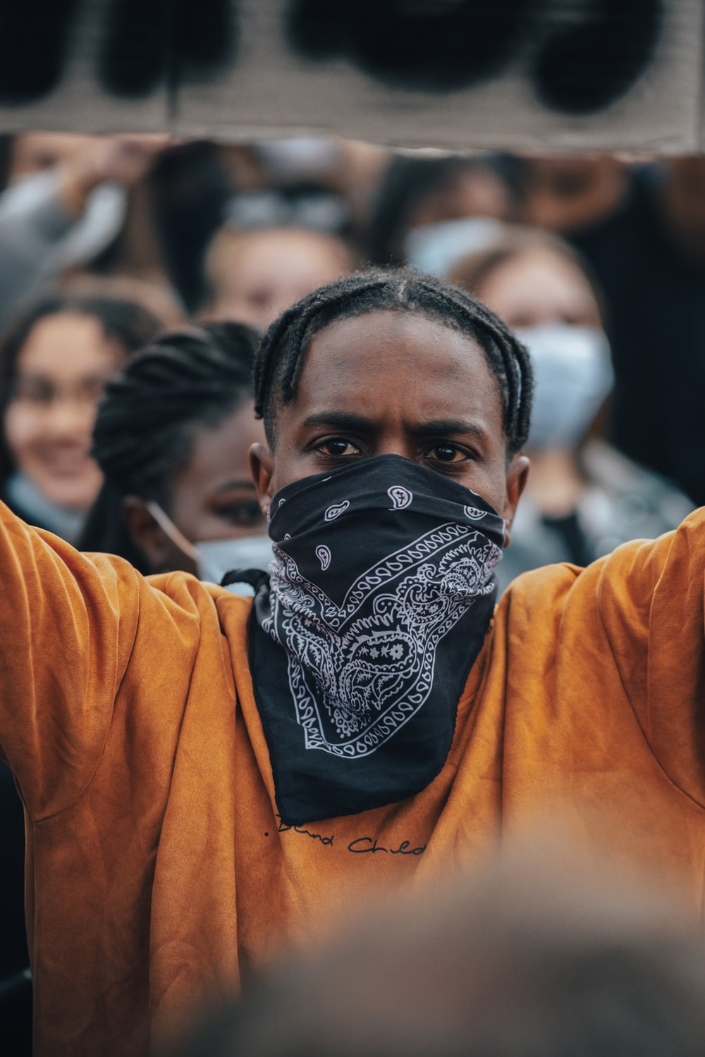 man in orange long sleeve shirt with black and white mask