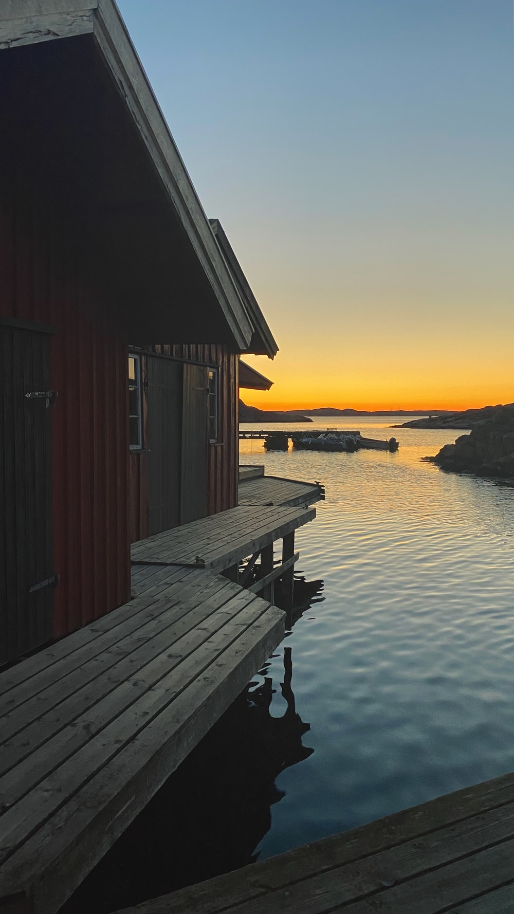 brown wooden house on sea dock during sunset