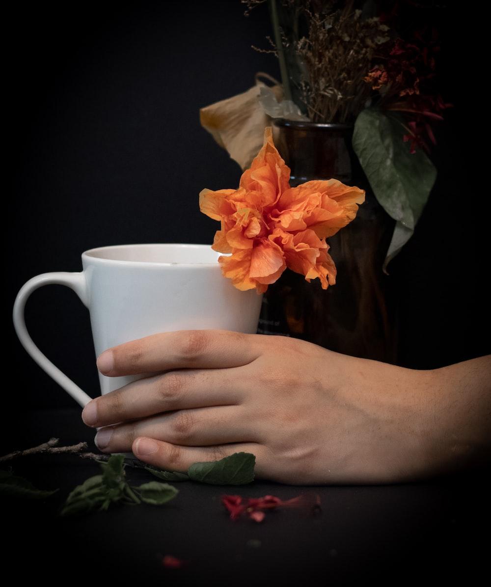person holding white ceramic mug with orange flower
