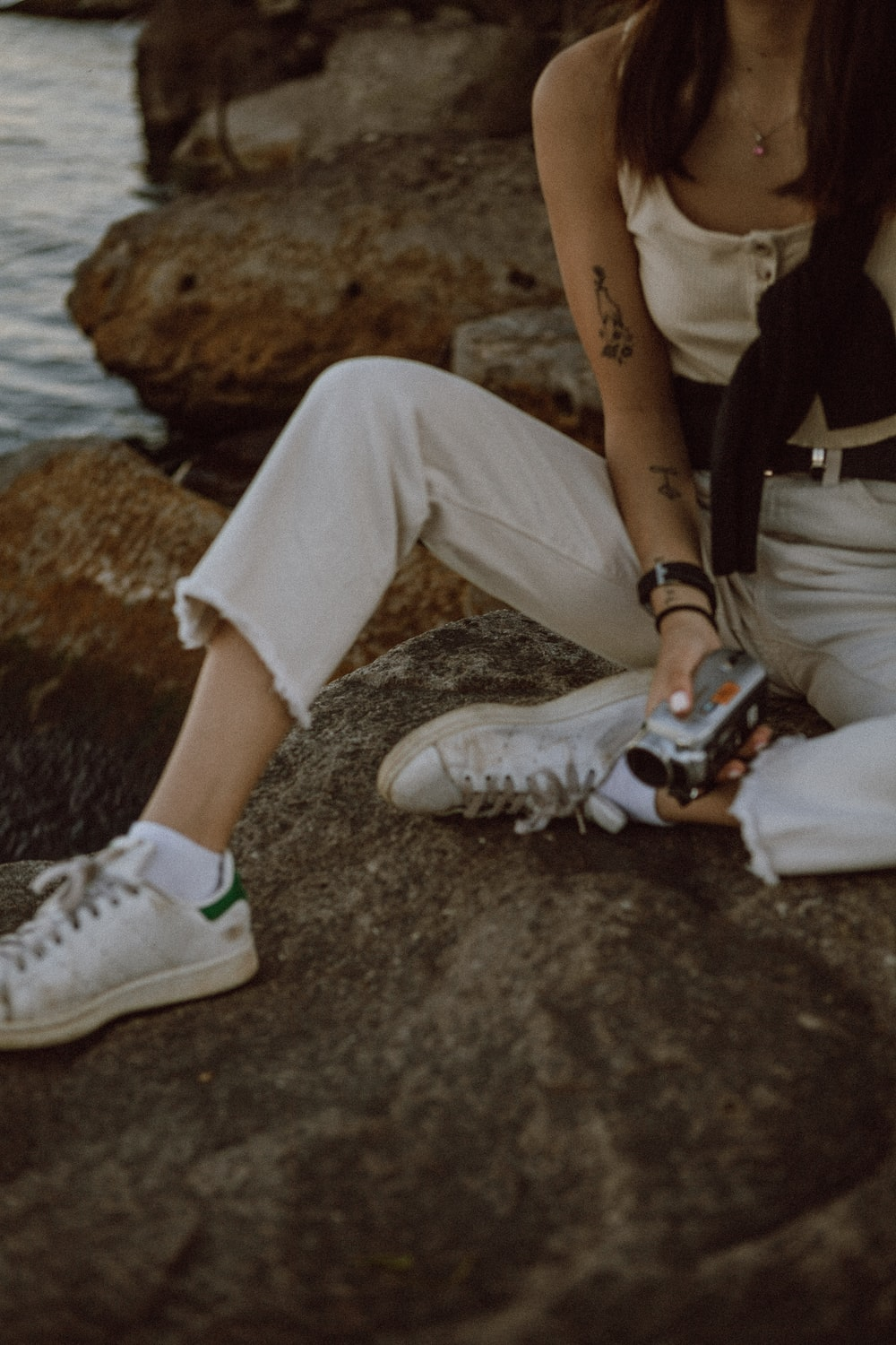 person in white pants and white nike sneakers sitting on rock