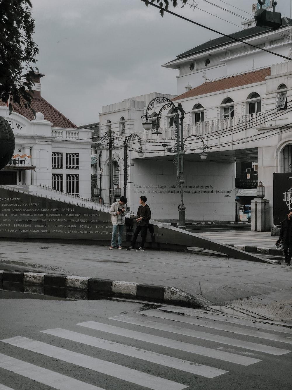2 women walking on sidewalk during daytime