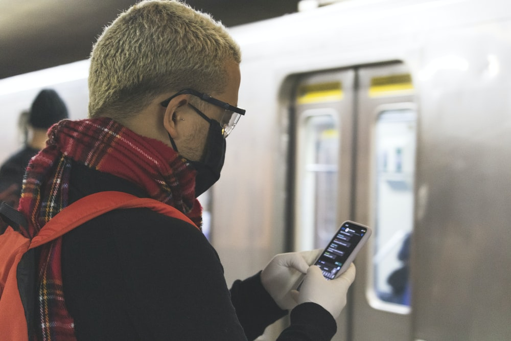 man in black and red jacket wearing black framed eyeglasses holding black and white candybar phone