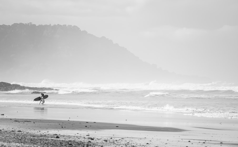 grayscale photo of person walking on beach