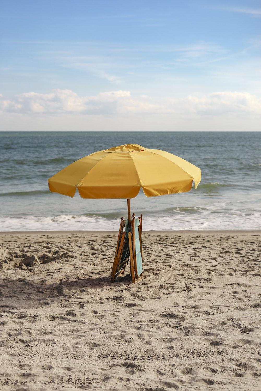 yellow umbrella on beach during daytime