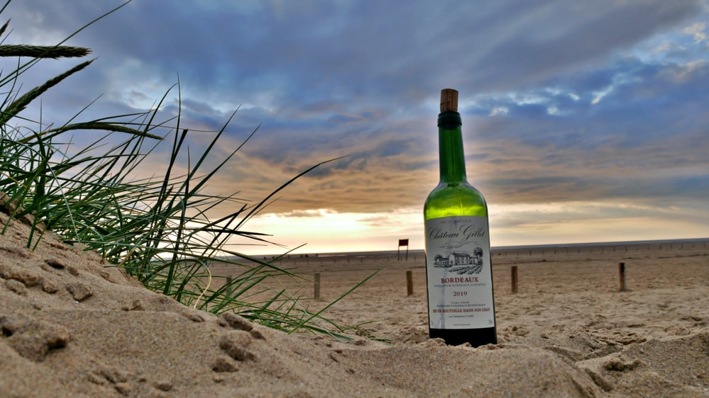 green glass bottle on brown sand during sunset