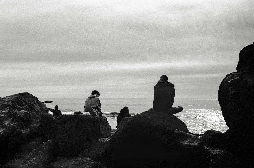silhouette of people sitting on rock near body of water