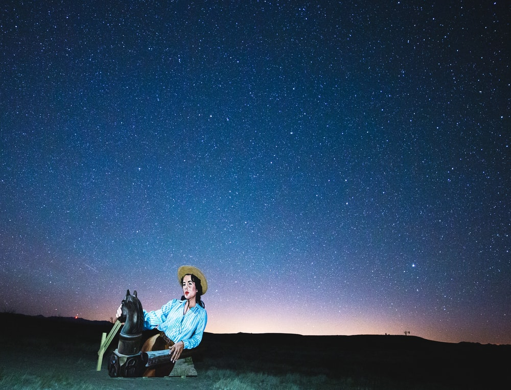 man in blue jacket sitting on black camping chair under blue sky during night time