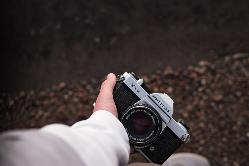 person holding black and silver dslr camera