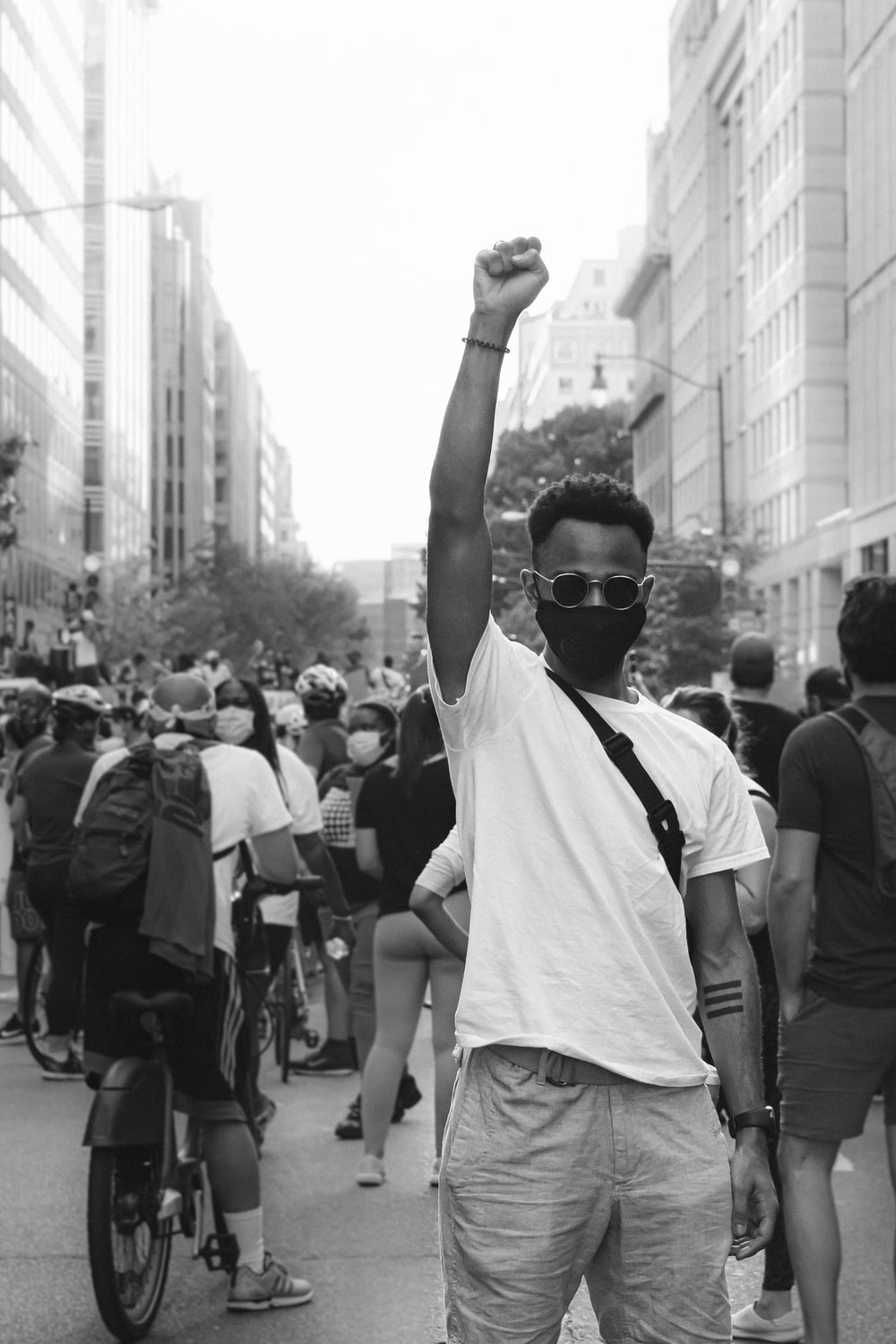 grayscale photo of man in white t-shirt raising his hands