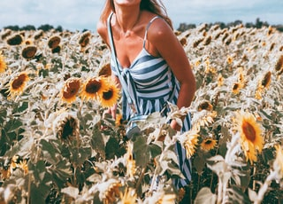 woman in white and blue stripe tank top standing on brown dried leaves during daytime