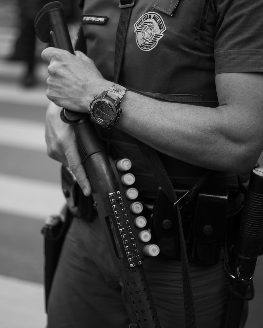 grayscale photo of man in police uniform holding rifle