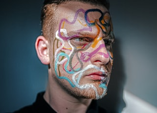 man with face paint wearing black zip up jacket