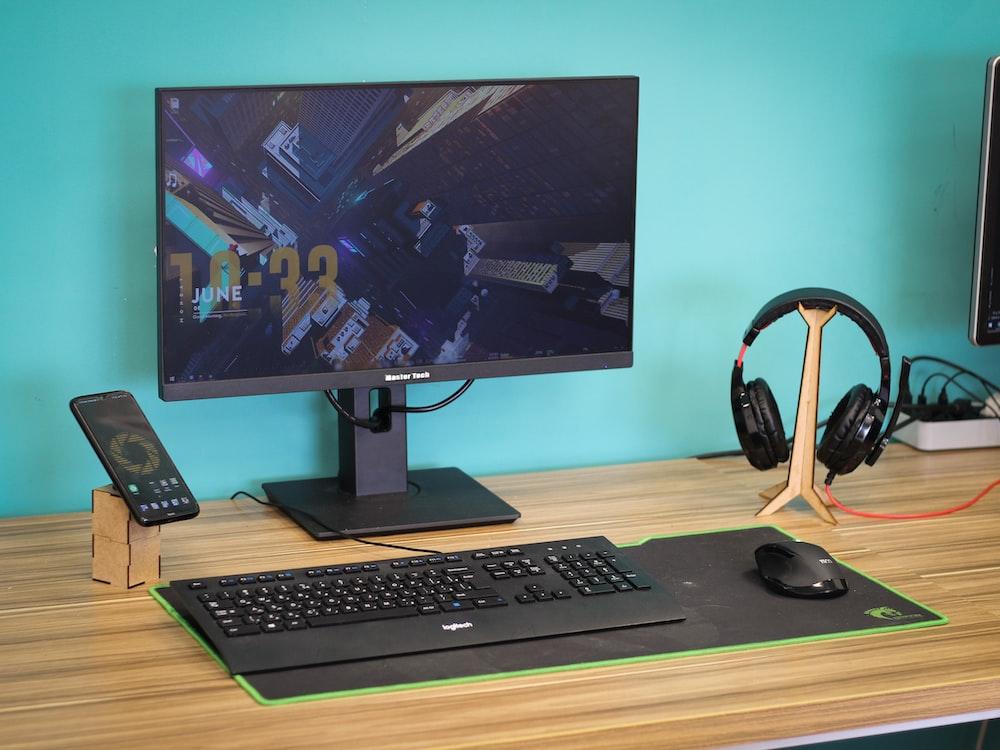 black flat screen computer monitor and black computer keyboard