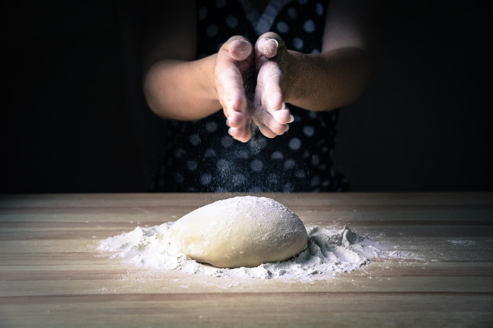 person holding dough on white table