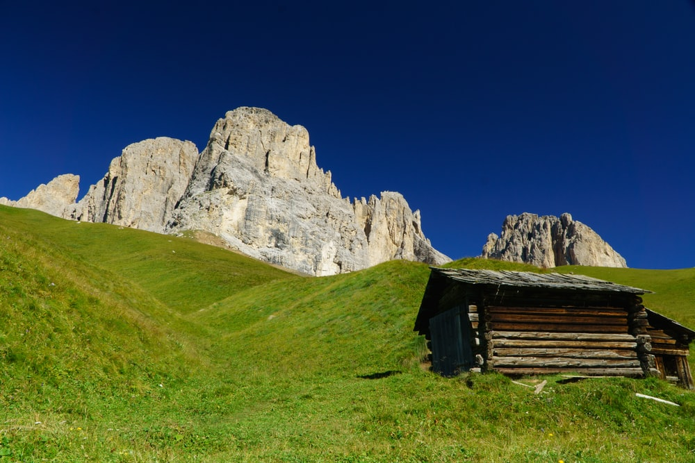 brown wooden house on green grass field near gray rocky mountain under blue sky during daytime