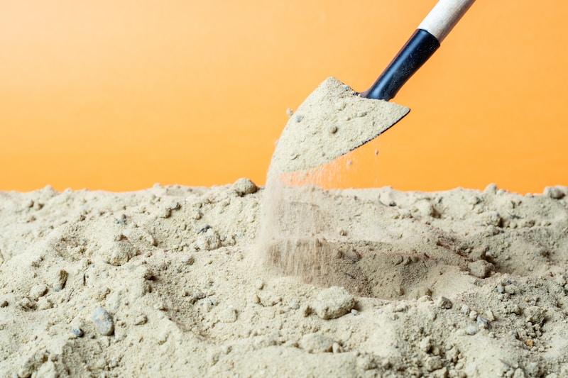 black and red shovel on white sand