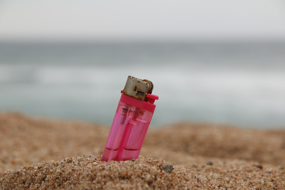 pink disposable lighter on brown sand