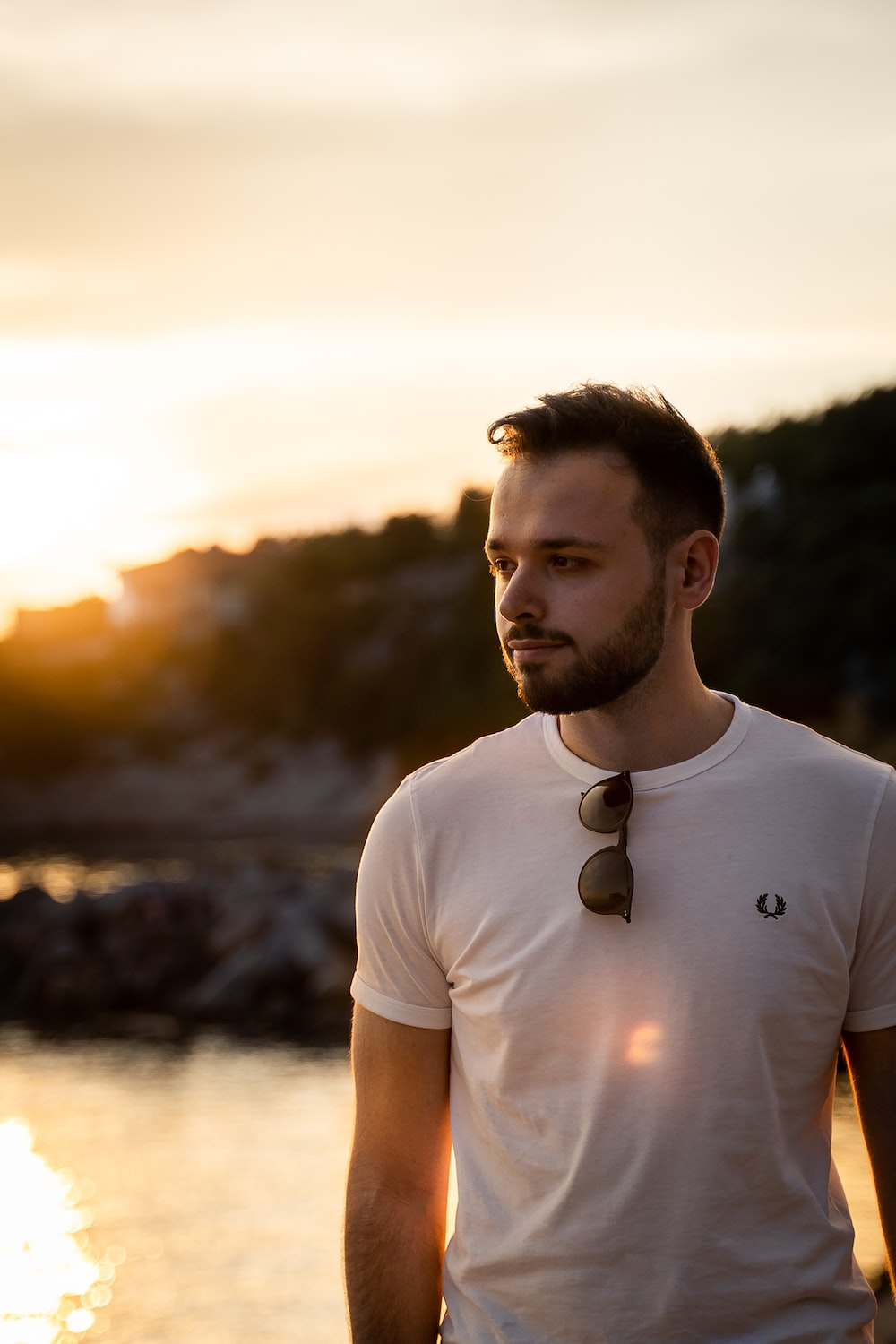 man in white crew neck t-shirt standing near body of water during daytime