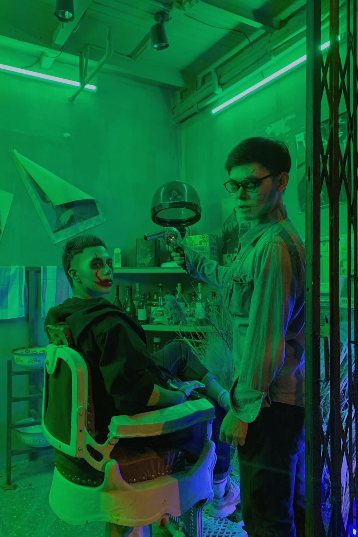 man in green dress shirt sitting beside woman in blue denim jacket
